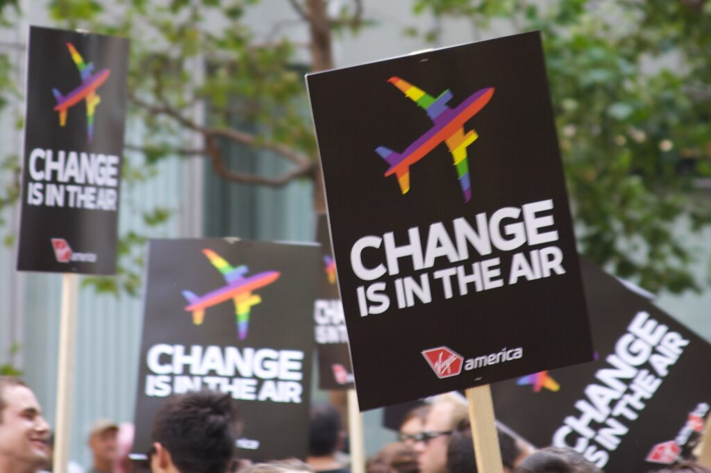 """Signs with an airplane icon with rainbow coloring; words """"Change is in the air"""" below"""